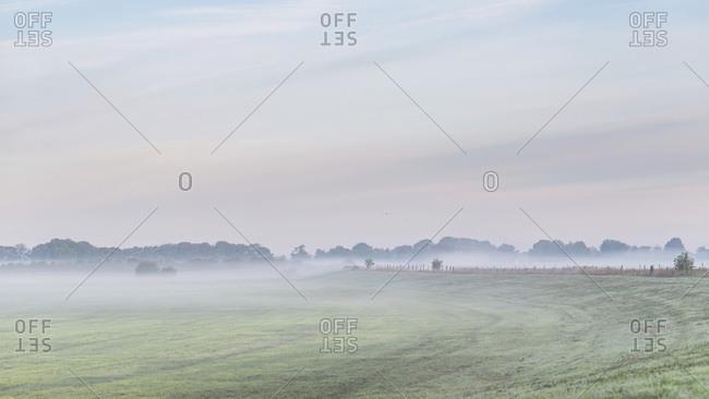 Hazy sunrise over vast farmland