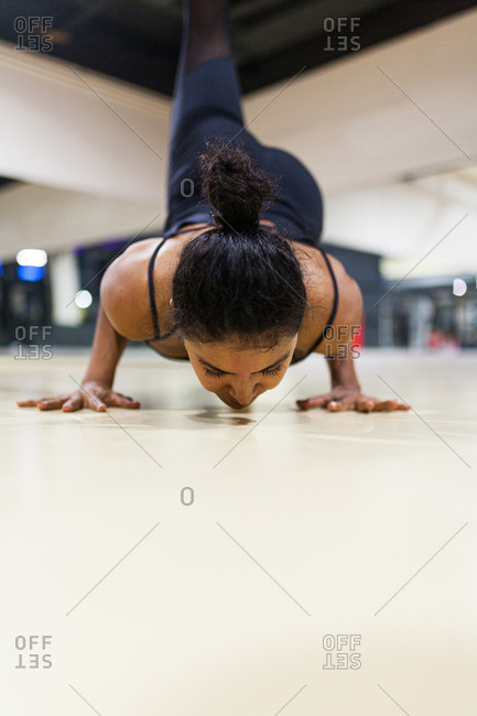 Young latin woman doing yoga poses with black clothes in her studio