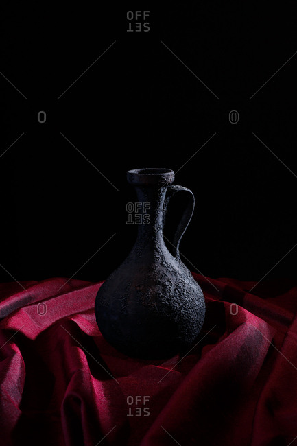Vessel on red cloth and black background