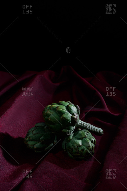 Artichokes on red cloth and black background