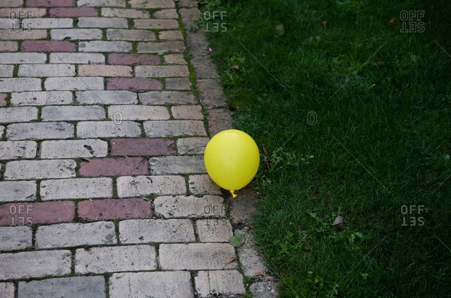 Yellow balloon floating between brick walkway and green grass