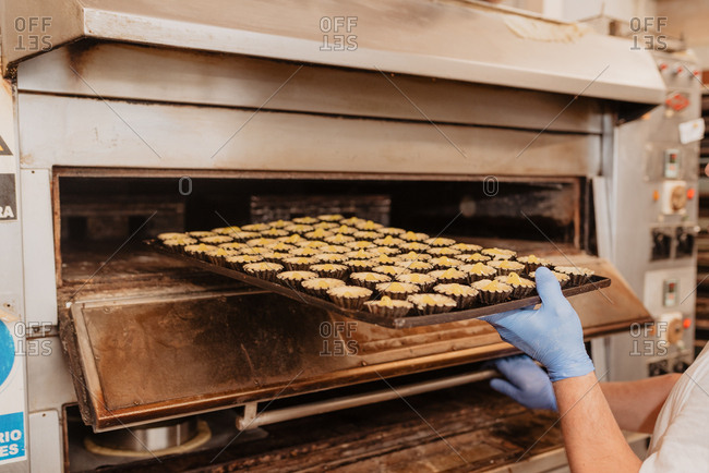 Crop bakery worker in latex gloves putting tray with empty pastry cases into professional oven