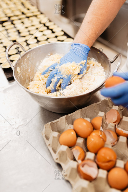 Crop confectioner in gloves and uniform mixing and kneading soft fresh dough while preparing pastry in bakery