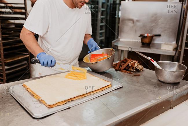 Bakery worker in latex gloves spreading sweet jam on fresh bun over kitchen counter