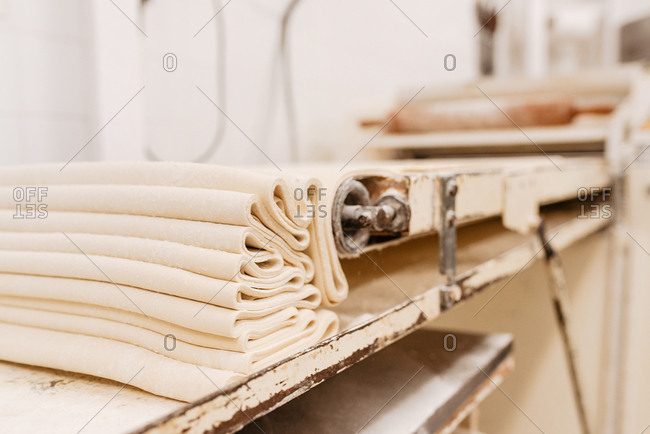Shabby machine rolling fresh soft dough for pastry preparation in kitchen of professional bakery