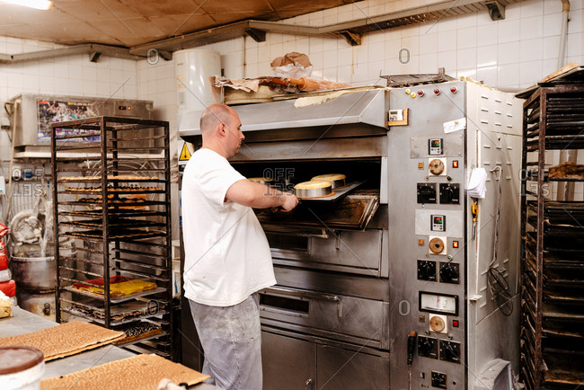 Man in uniform putting tray with raw cakes into hot oven while working in bakery