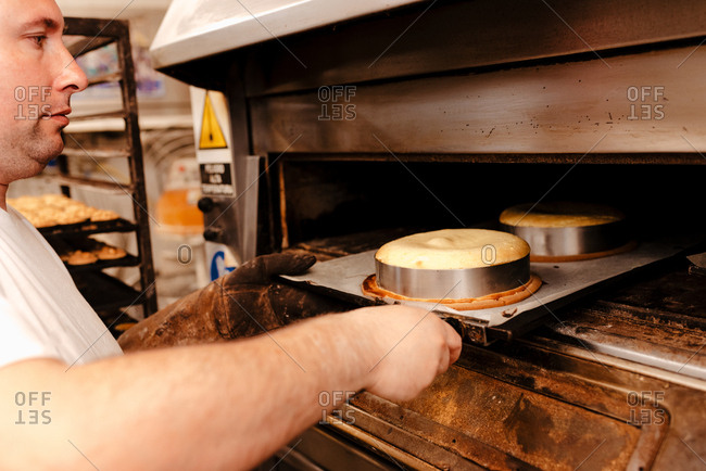 Crop adult man in uniform putting tray with raw cakes into hot oven while working in bakery