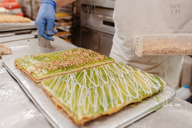 Unrecognizable confectioner in glove decorating delicious fresh cake with pastry crumbs while working in kitchen of bakery