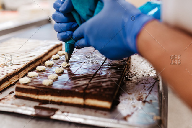 Closeup anonymous employee in gloves squeezing cream on top of fresh chocolate cakes on tray in bakery