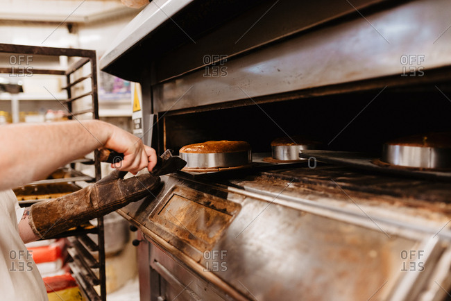 Man peeking inside professional oven while working in bakery