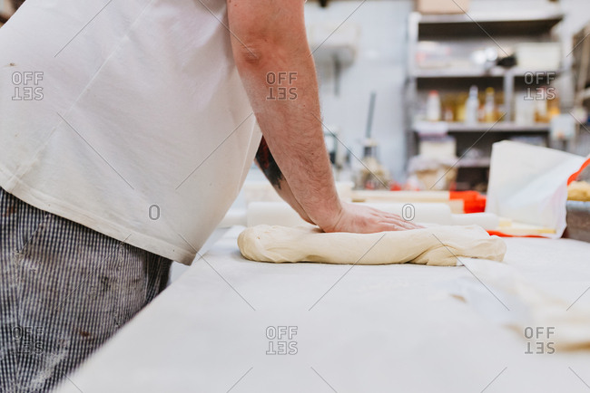 Side view of crop overweight man in uniform kneading soft dough on table while working in bakery kitchen