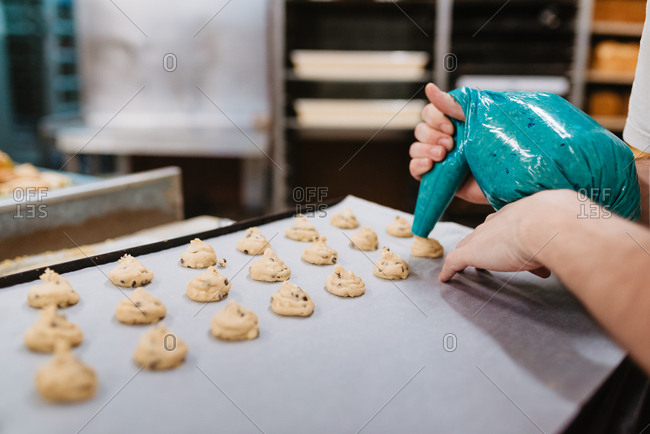Anonymous cook squeezing fresh pastry dough on tray with paper while working on blurred background of bakery