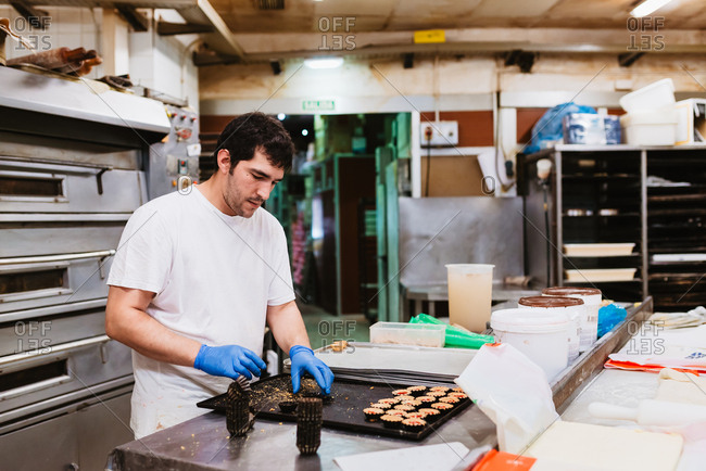Cook squeezing fresh pastry dough on tray with paper while working on blurred background of bakery
