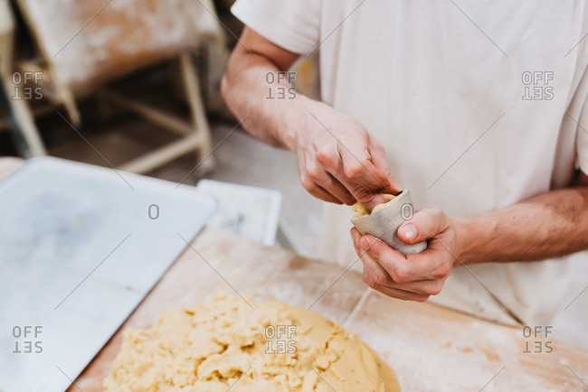 From anonymous confectioner putting fresh soft dough in small cup over table in bakery kitchen