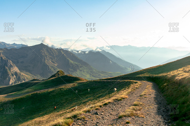 Dirt path extending inland to mossy mountains in foggy mist under cloudy sky