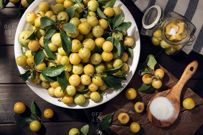 Fresh yellow plum mirabelle fruit in bowl on wooden table. preparing plum marmalade