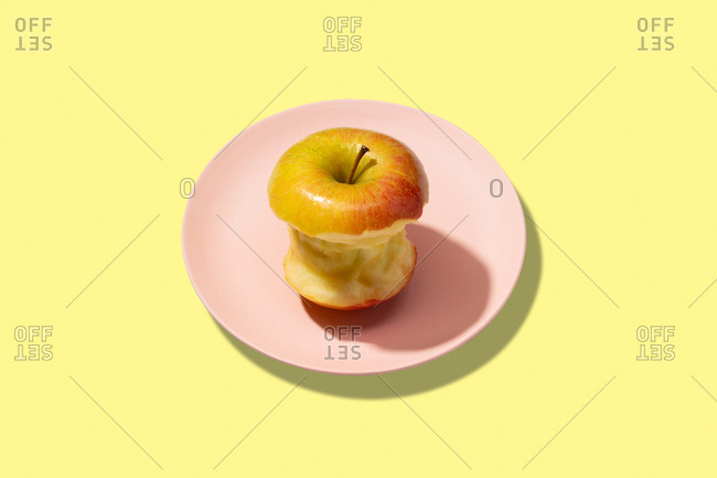 Fresh bitten apple in plate on yellow background. vibrant colorful pattern