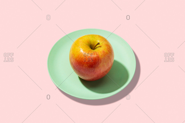 Fresh apple in plate on pink background. vibrant colorful pattern
