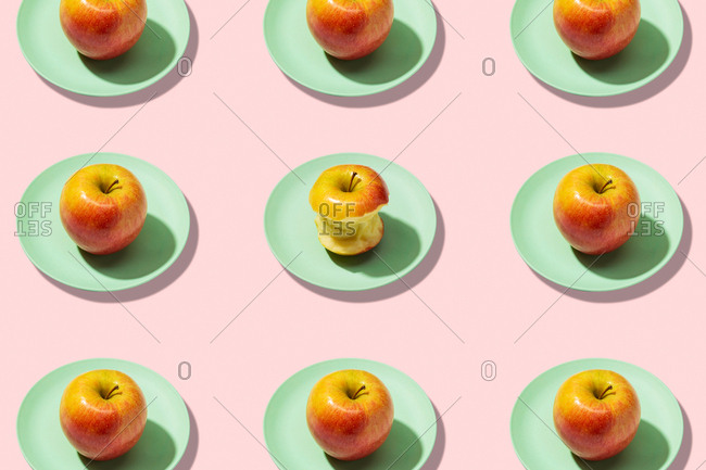 Fresh apples and bitten apple in plate on pink background. vibrant colorful pattern
