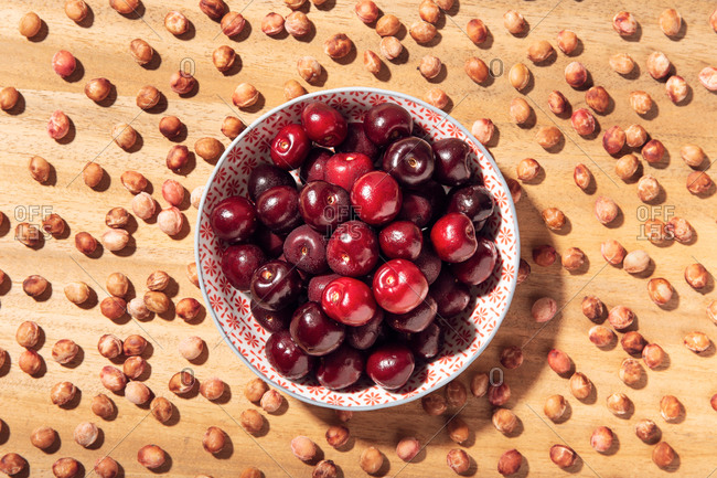 Top view of fresh sweet cherries in bowl with cherry seeds around on wooden table