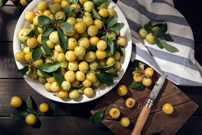 Fresh yellow plum mirabelle fruit in bowl on wooden table