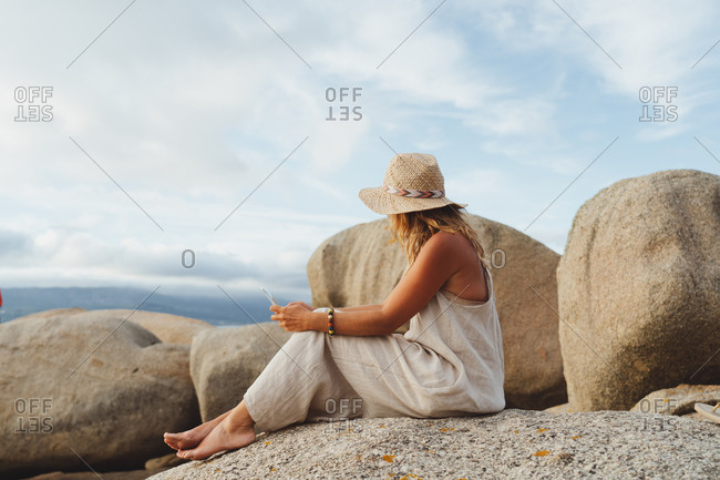Modern woman in straw hat sitting on coastal stone and holding smartphone while enjoying holidays