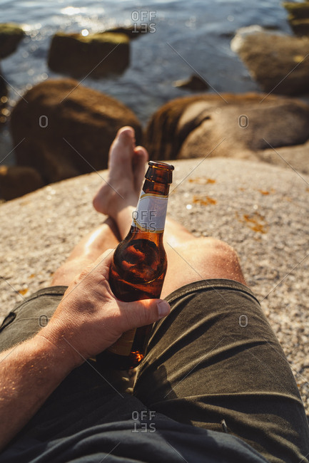 Crop man holding shiny bottle of beer resting sitting in stone on remote seashore