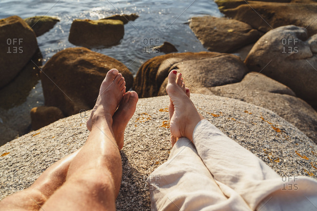 Crop feet of couple lying on warm stone on seashore and resting in glowing summer light