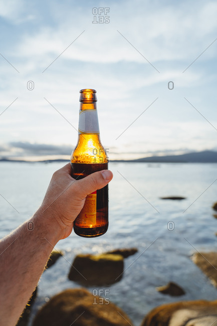 Crop traveling person holding shiny bottle of beer against sunlight resting on remote seashore