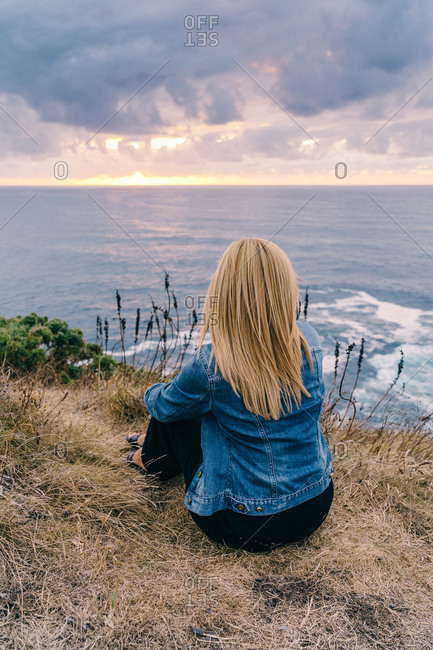 Back view of blond woman chilling and contemplating scenic seascape while sitting alone on calm seashore in clouds
