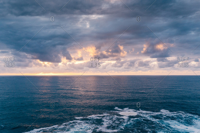 Overcast sundown sky over stormy sea with foamy waves in evening in nature
