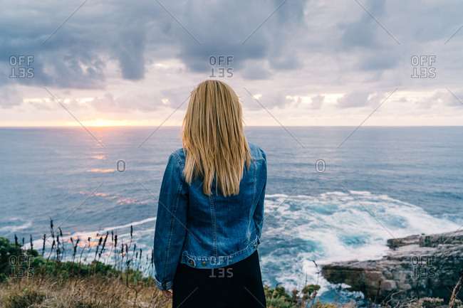 Back view of blond woman chilling and contemplating scenic seascape while standing alone on calm seashore in clouds