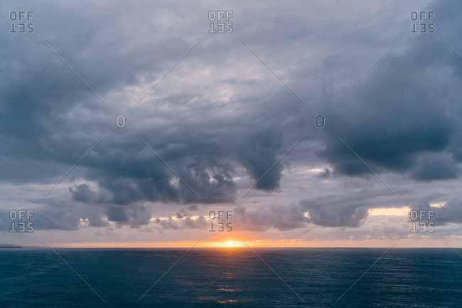 Coast with dry grass near stormy sea in cloudy evening during beautiful sunset