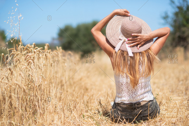 Back view of slim female touching hat while sitting on dry grain grass in meadow on sunny summer day in nature