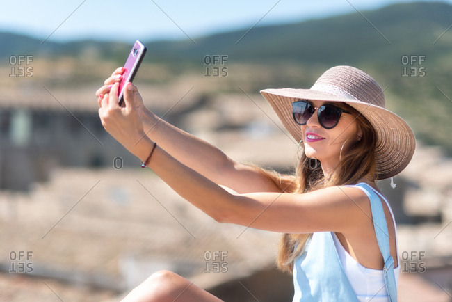 Positive woman in hat taking selfie on smartphone while standing on street