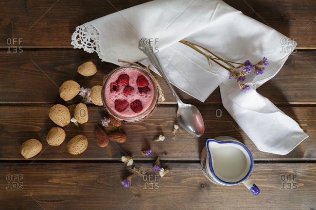 Top view of a raspberry smoothie in glass jar with almond milk served on rustic table with napkin