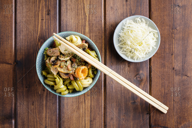 Organic pasta with vegetables in bowl and sushi chopsticks on wooden desk with bowl of side dish