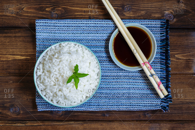 From above rice in bowl on blue towel with soy sauce and sushi chopsticks on rustic table