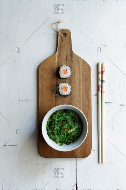 From above flat lay of sushi with seaweed salad in bowl on cutting board and chopsticks on rustic table