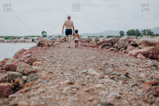 Back view of elderly man and small girl spending time on stony beach on cliff