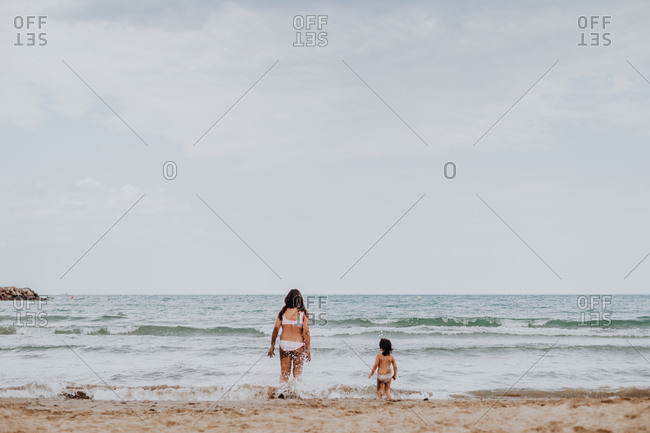 Back view of young woman and small kid enjoying foamy waves standing on sandy wet seaside
