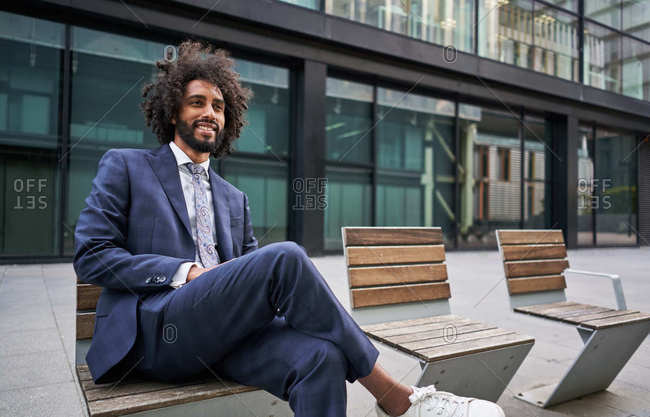 Optimistic and merry african american entrepreneur with beard sitting on bench with crossed legs and looking away