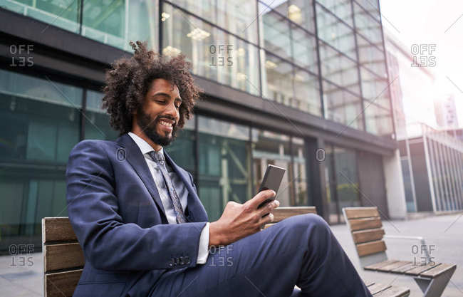 Joyful ethnic man in suit sitting outside and messaging