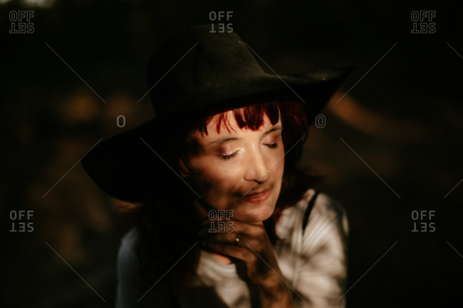 Thoughtful woman enjoying the moment with closed eyes alone in the forest