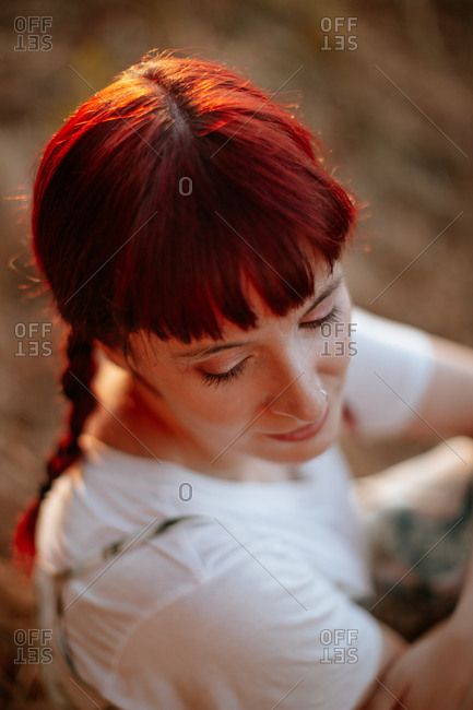 From above attractive lady with red braided hair closing eyes while sitting on blurred background of field ground in evening