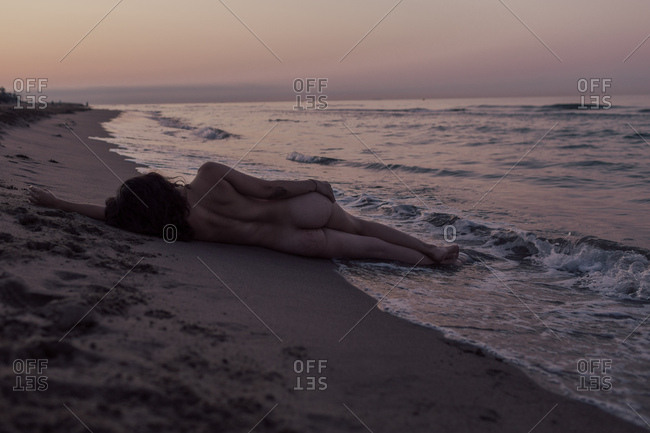 Back view of attractive sexy woman lying down on sandy beach enjoying beautiful seascape at sunset on nature background