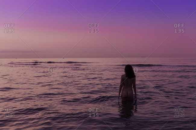 Back view of sexy woman with raised hands standing in water and enjoying landscape on gradient pink purple sky background