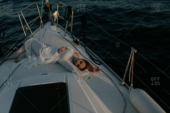 Relaxed beautiful lady lying on bow of ship and resting while enjoying sea trip with closed eyes