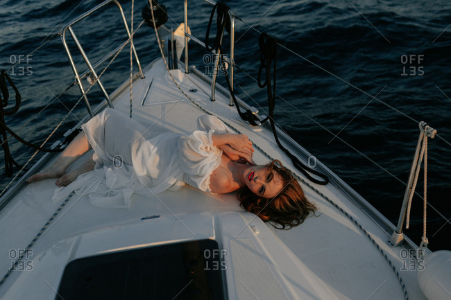 Relaxed beautiful lady lying on bow of ship and resting while enjoying sea trip looking at camera