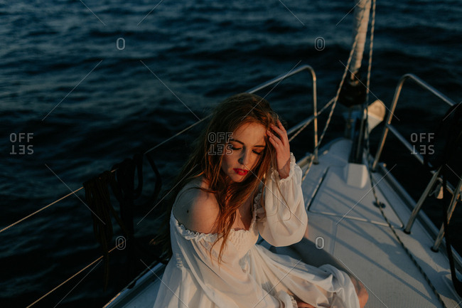 Relaxed beautiful lady sitting on bow of ship and resting while enjoying sea trip with closed eyes